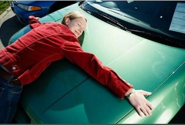 Девушка обнимает автомобиль